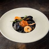Black Pasta Nero With Seafood, Spaghetti With Shrimp, Squid And Red Caviar. Beautiful Tasty Dish poster