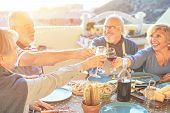 Happy Senior Friends Having Fun Cheering With Red Wine At Barbecue In Terrace Outdoor - Older People poster