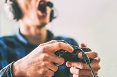 Young Man Having Fun Playing Video Games Online Using Headphones And Microphone - Close Up Male Hand poster