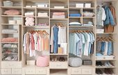 Stylish Clothes, Shoes And Accessories In Large Wardrobe Closet poster
