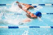 Men swimming butterfly stroke in a race, focus on water droplets, swimmers have motion blur poster