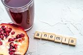 Cut Pomegranate And Pomegranate Juice On A White Background. Anemia Concept. Close-up poster