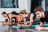 Concentrated Sporty Young Men And Women Doing Plank Exercise On Yoga Mats In Gym poster