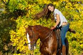 image of straddling  - Beautiful girl  straddling a horse in garden - JPG