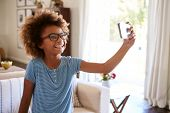 Pre-teen girl taking a selfie photo standing in the living room laughing, close up, focus on foregro poster