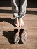 Feet Of A Woman In Funny Home Made By Hand Slippers On The Wooden Warm Floor Background. Cozy Home A poster
