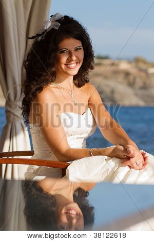 Bride Sitting At The Table Near Water
