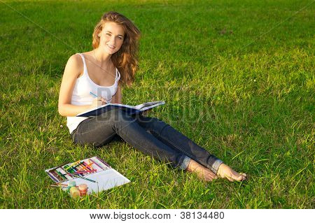 Young Woman Painting On A Green Meadow