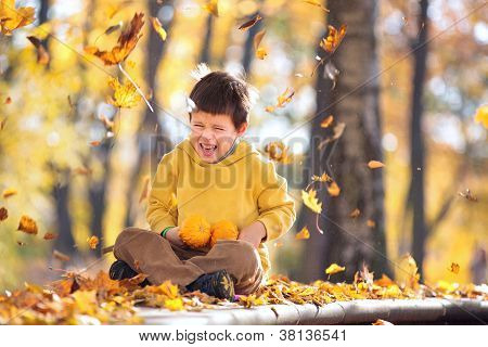 Cute five years old boy having fun in autumn park