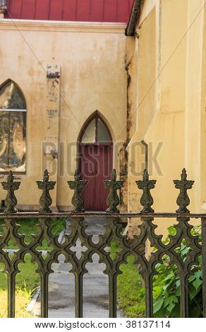 Wrought Iron Fence Before Red Church Door