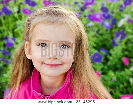 Outdoor Portrait Of Cute Little Girl Near The Flowers