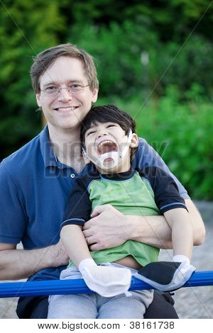 Father Holding Disabled Son At Playground