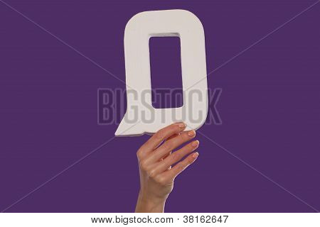 Female Hand Holding Up The Letter Q From The Bottom