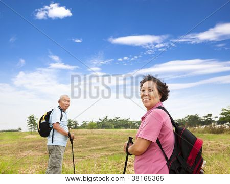 Happy Asian Senior Couple Hiking In The Nature