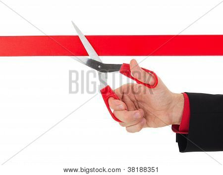 Human Hand Cutting The Red Ribbon With Scissors