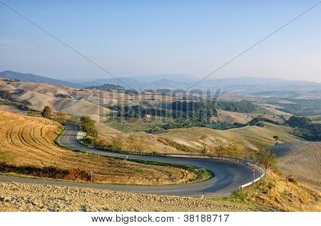 Winding road in autumn Tuscany Italy