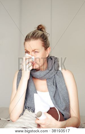 Woman Ill In Bed Blowing Her Nose