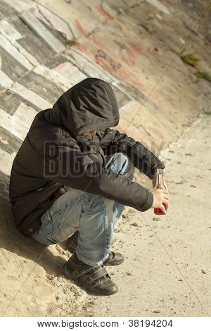 Boy with a bottle of hands sit on a concrete wall