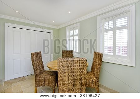 Modern dining room with round wooden table and rattan chairs
