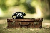 image of old suitcase  - vintage suitcase with phone on meadow inspired by old memories and departures - JPG