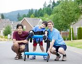 picture of street-walker  - Disabled boy in walker surrounded by father and older brother while walking outdoors on street - JPG