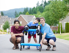 image of street-walker  - Disabled boy in walker surrounded by father and older brother while walking outdoors on street - JPG