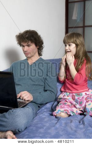 Father And Daughter Playing Game Sitting On The Sofa Using A Laptop Computer