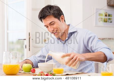 Happy Young Man Pouring Milk Into Bowl For Breakfast