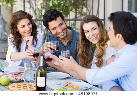 Group Of Happy Young Friends Toasting Wine Glass Outdoor While Having Lunch