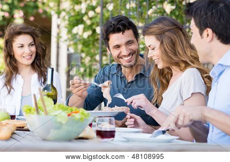 Group Of Happy Young Friends Having Dinner At Patio