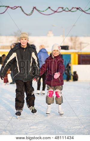Boy and girl skating on rink hand in hand in winter