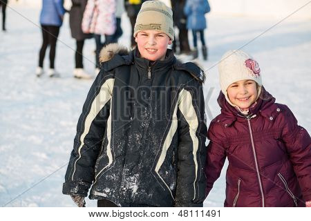Brother and sister skating hand in hand in winter