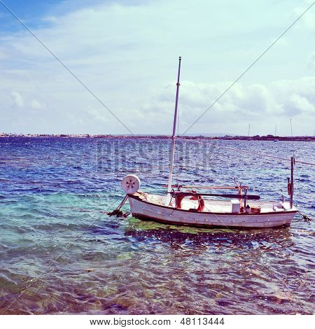 picture of a fishing boat in Estany des Peix lagoon, in Formentera, Balearic Islands, Spain, with a retro effect
