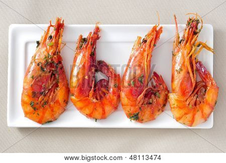 closeup of a plate with spanish shrimps cooked with garlic and parsley
