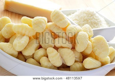 closeup of a pile of gnocchi and a bowl with grated parmesan cheese