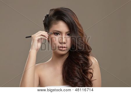 Female Asian Applying Eye Shadow