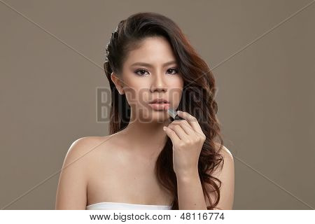 Female Asian Applying Lip Stick