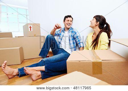casal comemorando nova casa entregando as chaves e caixas de mudança