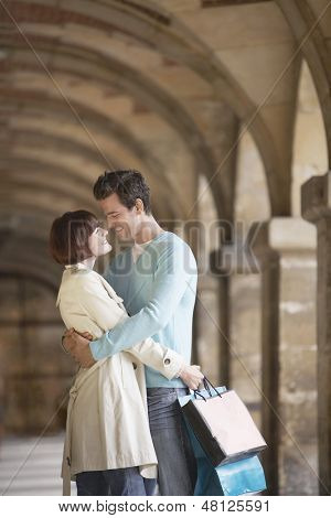 Side view of a couple with shopping bags embracing under archway