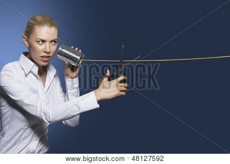 Businesswoman cutting line on tin can string phone against blue background