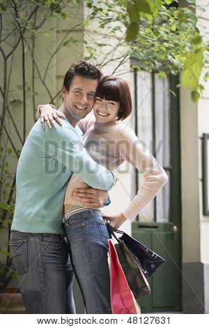 Side view of a couple with shopping bags embracing outdoors