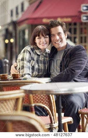 Portrait of a happy young couple sitting at an outdoor cafe