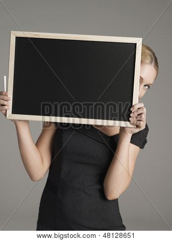 Portrait of a young female teacher peeking from behind blackboard against gray background