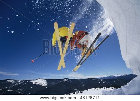 Low angle view of two skiers launching off snow bank hitting the slopes