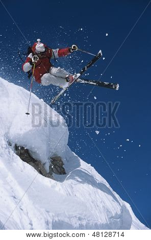 Low angle view of a skier in midair above snow on ski slope