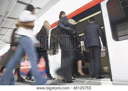 Low angle view of business commuters getting into a train