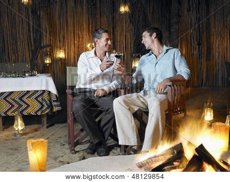Two men sitting by bonfire at outdoor nightclub toasting