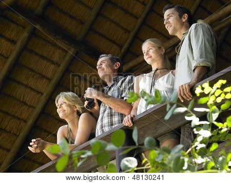 Low angle view of two couples on terrace with binoculars