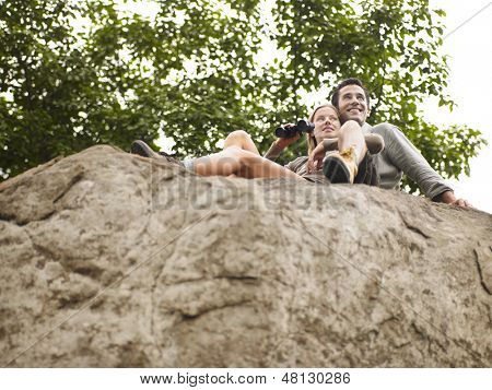 Low angle view of a young man and woman on rock with binoculars looking at view