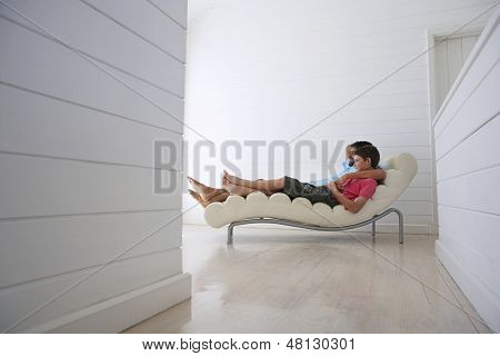 Side view of young boy with father reclining on lounge chair at home